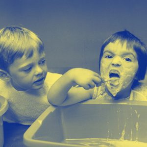 two kids with toothpaste all over their faces near a sink