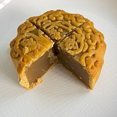 A moon cake with an ornamental design on its crust and a wedge cut out as revealing the inside of the dessert