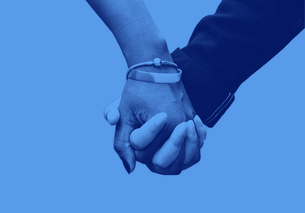image of two hands holding each other on a blue blackground.