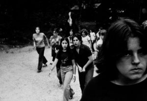 black and white photo of group of children and young people outside near trees, with a shadowy, mysterious figure in the back