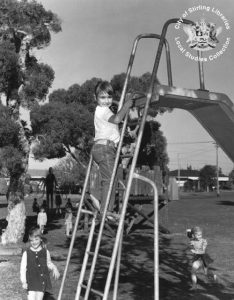 black and white photo of a child climbing the steps of a slide in a park, with a shadowy figure with long arms in the distance